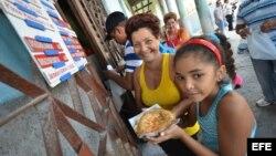 Varias personas compran pizzas en una cafetería gestionada por trabajadores por cuenta propia en La Habana.