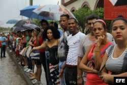 Un grupo de cubanos observa la llegada del presidente de los EEUU Barack Obama a Cuba a través de la señal de televisión captada por un teléfono móvil