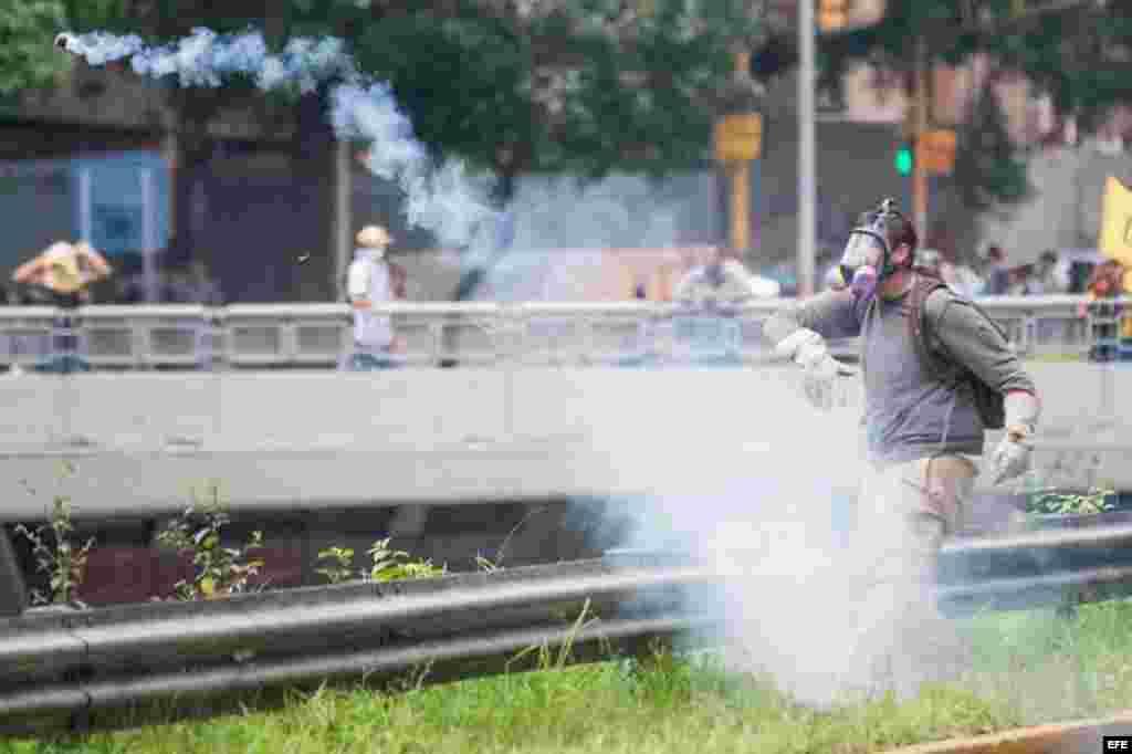 Un manifestante devuelve una granada de gases lacrimógenos lanzada por miembros de la Policía Nacional Bolivariana (PNB) durante una protesta hoy, miércoles 18 de mayo de 2016, en la ciudad de Caracas (Venezuela).