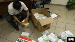 Foto de archivo. Un miembro de la Dirección General de Servicios Especiales de Investigación de Honduras revisa papeles migratorios.
