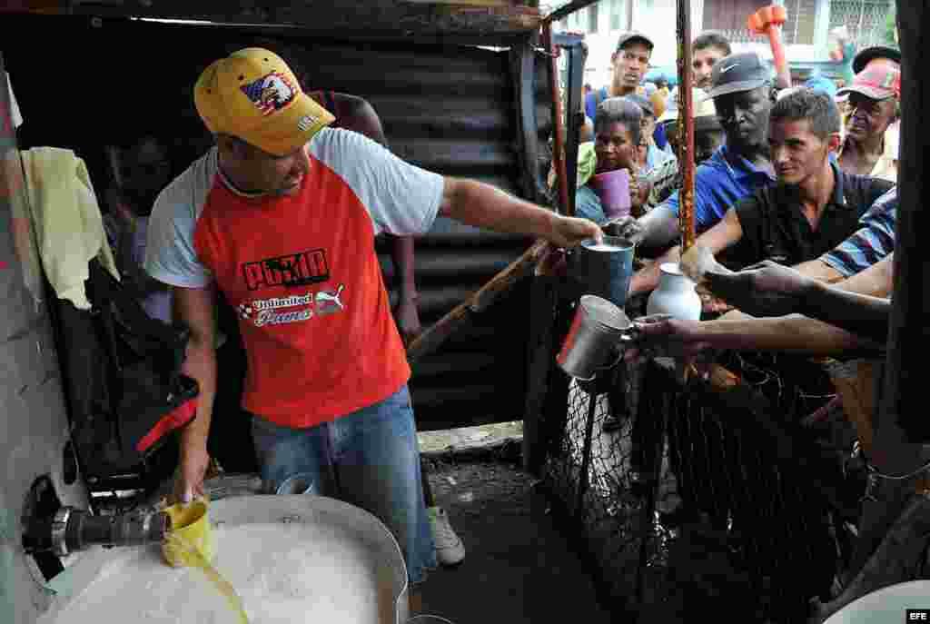 Varias personas compran cerveza en Santiago de Cuba.