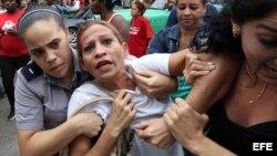Una integrante de la Damas de Blanco es detenida, entre hostigamiento e insultos de sectores oficialistas, el 10 de diciembre de 2015, en La Habana (Cuba)