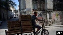 Un hombre transporta frutas para vender en La Habana, el 22 de junio de 2020. (Yamil Lage / AFP).