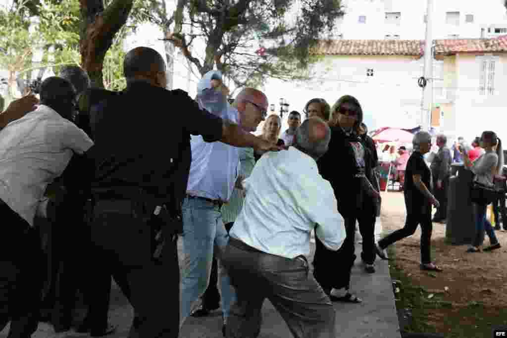 Al ventro Orlando Gutiérrez Boronat, del Directorio democrático Cubano, flanqueado por agentes de la embajada cubana en Panamá.