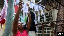 Una mujer tiende nasobucos preparados por ella misma para distribuir entre vecinos del Vedado (Foto: Adalberto Roque/AFP).