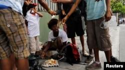 Un grupo de jóvenes come de una torta después de hallarla en una bolsa de basura en Caracas, Venezuela, el 27 de febrero de 2019.