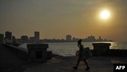 Una mujer camina con mascarilla por el malecón de La Habana.