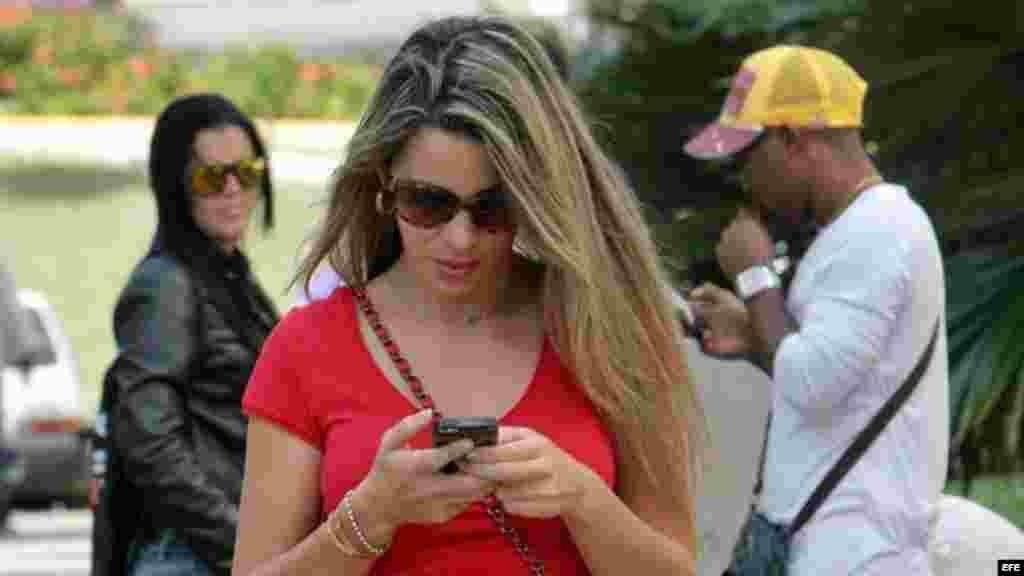 Una joven revisando su teléfono celular en una calle de La Habana.