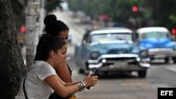 Dos mujeres navegan por internet usando una red wifi en La Habana (Cuba).
