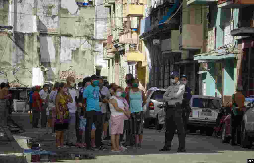 Policías en La Habana controla hilera de compradores en tiendas para comprar con dólares de EEUU.