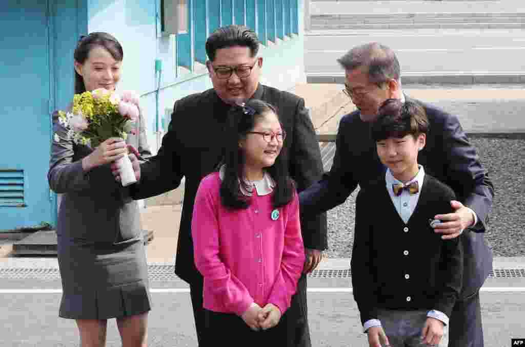 Kim Yo Jong, con un ramo de flores, junto a su hermano Kim Jong Un y el presidente de Corea del Sur, Moon Jae-in, posan con niños después de reunirse en la zona desmilitarizada de Panmunjom, el 27 de abril de 2018. (Korea Summit Press Pool/ AFP)