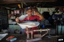 Un hombre despacha arroz en una bodega de San Luis en Santiago de Cuba.