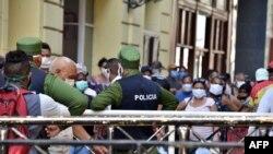 Cubanos se aglomeran en un mercado de La Habana, bajo la vigilancia de agentes de la policía, para comprar alimentos, el 12 de abril del 2020.