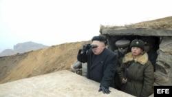 Fotografía distribuida por la agencia Yonhap que muestra al jefe norcoreano, Kim Jong-un, observando con unos prismáticos durante su visita a una unidad militar situada en una isla muy próxima a Corea del Sur.
