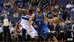 El jugador de Timberwolves Ricky Rubio (d) es marcado por Nene Hilario (i), de Wizards, durante un partido por la NBA, en el Verizon Center de Washington (DC, EE.UU.).