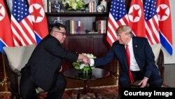 Saludos entre Donald Trump y Kim Jong-Un en una de las salas del Hotel Capella