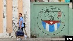 Una pareja camina junto a un cartel con el emblema de los Comités de Defensa de la Revolución (CDR), en La Habana, Cuba.