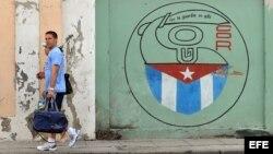 Una pareja camina junto a un cartel con el emblema de los Comités de Defensa de la Revolución en La Habana.