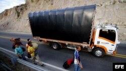 Migrantes venezolanos en una carretera.