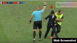 Un agente de seguridad detiene a una de las personas que invadió la cancha en la final del mundial de fútbol.