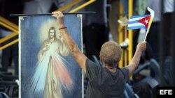 Una mujer cubana copn una imagen de Cristo y la bandera de su país en la Plaza de la Revolución de La Habana, donde el Papa oficiará su primera misa en Cuba, a la que asistirán miles personas que ya están congregadas en el que se considera uno de los luga