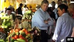 El secretario de Agricultura de Estados Unidos, Thomas Vilsack, conversa con comerciantes durante una visita a un mercado agropecuario.