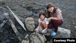 La esposa y la hija del fotógrafo Andrei Parfyonov posan con fragmentos de la estatua de Stalin.