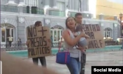 Nelva Ismarays Ortega Tamayo con su bebé en brazos reclama conocer el paradero de su esposo.