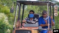 Dos cubanos viajan el martes en tractor por una calle de La Habana (Yamil Lage/AFP).