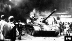 """Jóvenes checos se suben a un tanque de guerra soviético en una calle incendiada. El pueblo checoslovaco potestó en masa contra la invasión de su país, produciéndose huelgas y anifestaciones obreras, ciudadanas y estudiantiles en la denominada """"Primavera de Praga""""."""