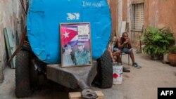 """Un cubano descansa junto a un camión cisterna """"pipa"""" donde han colocado un cartel con las figuras de Fidel y Raúl Castro el 9 de abril de 2018. (Archivo)"""
