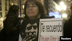 """An opponent of the late Chilean dictator Augusto Pinochet holds poster of Chilean singer Victor Jara, who was murdered during Pinochet's dictatorship, at Sant Jaume square in Barcelona December 11, 2006. The poster reads, """"I remind you, we all were Victo"""