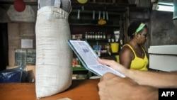 """Un hombre espera comida en una tienda mientras sostiene una """"libreta"""", una tarjeta de racionamiento que desde 1963 ha permitido a los cubanos comprar alimentos básicos."""