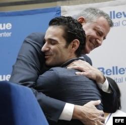 El alcalde de Nueva York Bill de Blasio (i) abraza al médico estadounidense Craig Spencer.