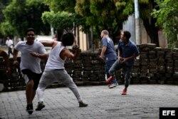 Manifestantes lanzan piedras durante enfrentamientos con la Policia Nacional en los barrios de Managua.