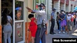 La polic[ia organiza la cola en una TRDd e Guantánamo. (Captura de foto/Venceremos)
