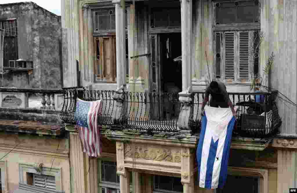 Un hombre cuelga una bandera de Cuba después de colgar la de EE.UU. hoy, lunes 21 de marzo de 2016, en La Habana (Cuba).