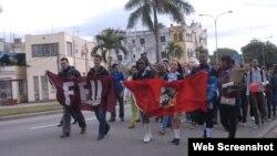 Adolescentes y jóvenes marchan por una calle de La Habana portando banderas de la UJC y la FEU.