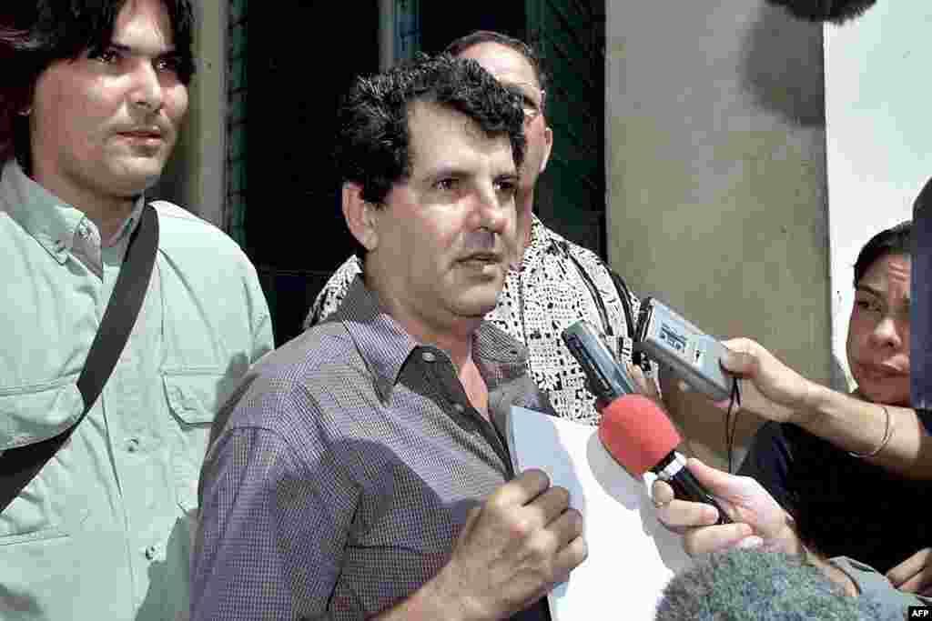 El disidente cubano Oswaldo Payá, del Movimiento Cristiano Liberación, habla con reporteros frente a la Asamblea Nacional en La Habana, el 10 de mayo de 2002.