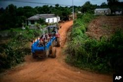 En esta fotografía del 24 de agosto de 2019, un tractor jala un remolque que fue convertido en una piscina a lo largo de las calles del vecindario de El Infernal, en la provincia de Pinar del Río, Cuba. (AP Foto/Ramon Espinosa)