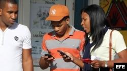 Jóvenes utilizan sus teléfonos celulares en Cuba.
