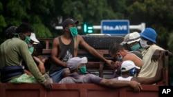Trabajadores con máscaras protectoras por el coronavirus viajan en un camión en La Habana. (AP/Ramon Espinosa)