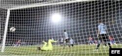 El portero uruguayo Fernando Muslera encaja un gol del defensa chileno Mauricio Isla.