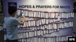 Un joven fotografía mensajes de apoyo a los pasajeros del vuelo desparecido de Malaysia Airlines en un centro comercial en Kuala Lumpur (Malasia).