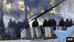 Varios policías antidisturbios montan un cordon policial tras una bandera de la Unión Europea cerca de una de las barricada un nuevo día de protestas contra el gobierno en el centro de Kiev (Ucrania).