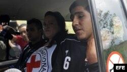 Los policías colombianos Víctor Alfonso González y Cristian Camilo Yate pasan junto a la prensa en un vehículo hoy, viernes 15 de febrero de 2013, luego de ser liberados por las FARC
