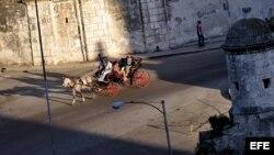 Turistas pasean en un coche de caballos por una avenida de la Habana Vieja.