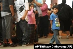 Niños hacen fila con algunos de los miles de jóvenes inmigrantes en el Navy Pier de Chicago. Foto: AP/Sitthixay Ditthavong.