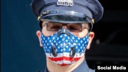 Policía estadounidense usa un tapabocas con la bandera americana