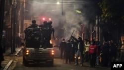 Bolivianos saludan en una calle de La Paz la noche del domingo a un vehículo de la policía que patrulla la zona (Foto: Ronaldo Schemidt/AFP).